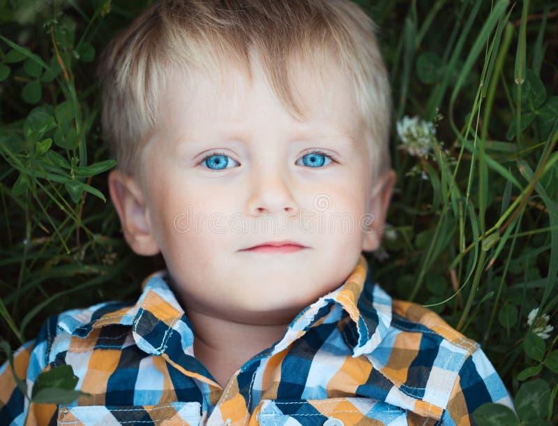 Un ragazzino sveglio che si trova in un campo di verde fotografia stock libera da diritti