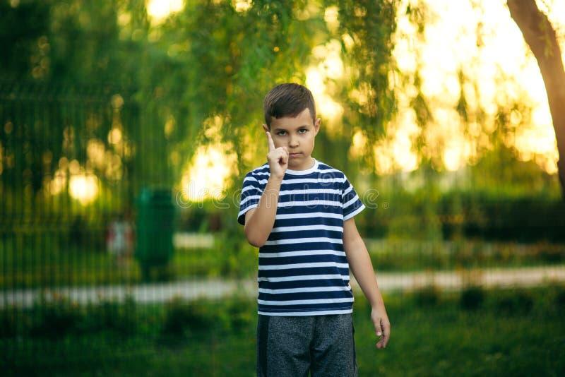 Un ragazzino in una maglietta a strisce sta sorridendo ed incoraggiando Primavera, tempo soleggiato immagine stock