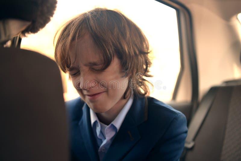 Un ragazzo è un adolescente con i capelli lunghi in un vestito classico nell'automobile fotografie stock