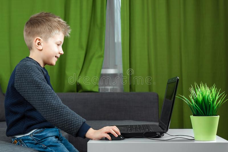 Un ragazzo ad un computer portatile gioca, o guarda un video Il concetto di dipendenza ai giochi di computer, offuscamento della  immagini stock