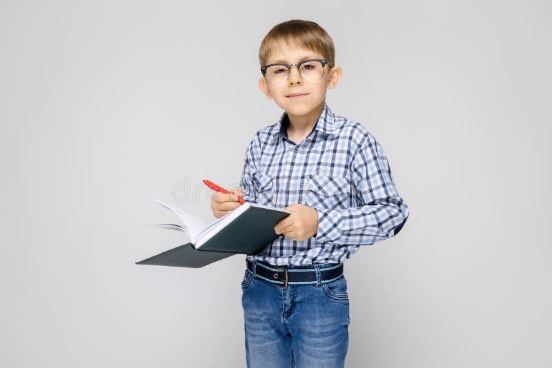 Un ragazzo affascinante con una camicia vkletchatoy ed i jeans della luce sta su un fondo grigio Il ragazzo tiene un taccuino e u immagini stock libere da diritti