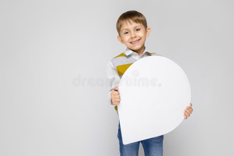 Un ragazzo affascinante in una camicia bianca, in una canottiera sportiva a strisce e nei jeans della luce sta su un fondo grigio fotografia stock