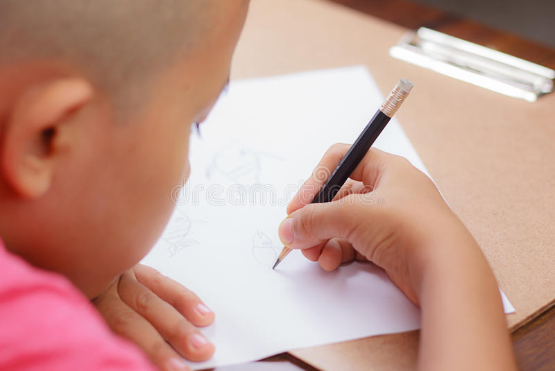 Un ragazzo asiatico sta scrivendo sul Libro Bianco fotografie stock libere da diritti
