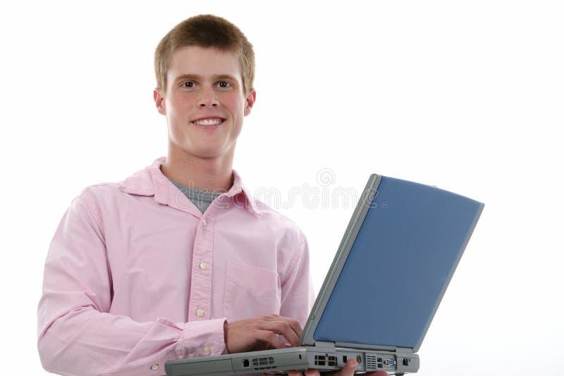 Un ragazzo attraente di sedici anni con il computer portatile fotografie stock libere da diritti