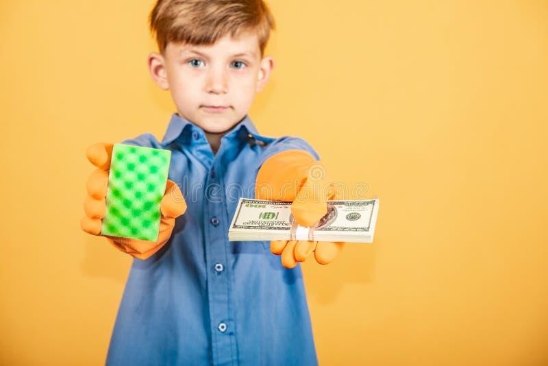 Un ragazzo bello in una camicia blu e nei guanti lavare tiene un pacchetto dei dollari in una mano ed in una spugna lavante nell' fotografia stock
