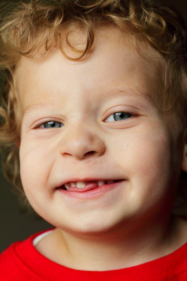 Un ragazzo biondo felice da 2 anni che manca un dente fotografia stock
