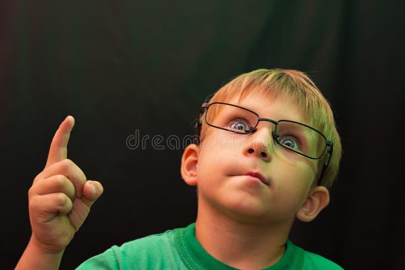 Un ragazzo casuale con i vetri ha alzato il suo dito su e cerca, contro un fondo scuro fotografia stock