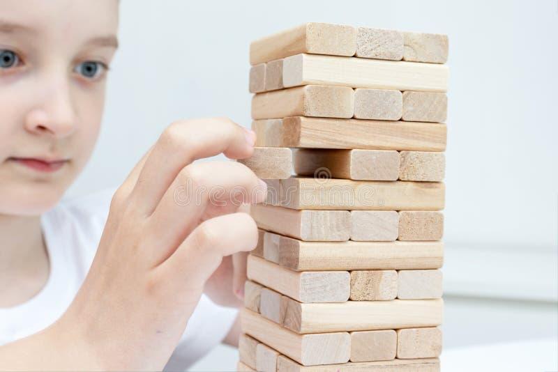 Un ragazzo caucasico preteen che gioca il gioco da tavolo di legno della torre del blocco per la pratica la suoi abilità e spetta fotografia stock