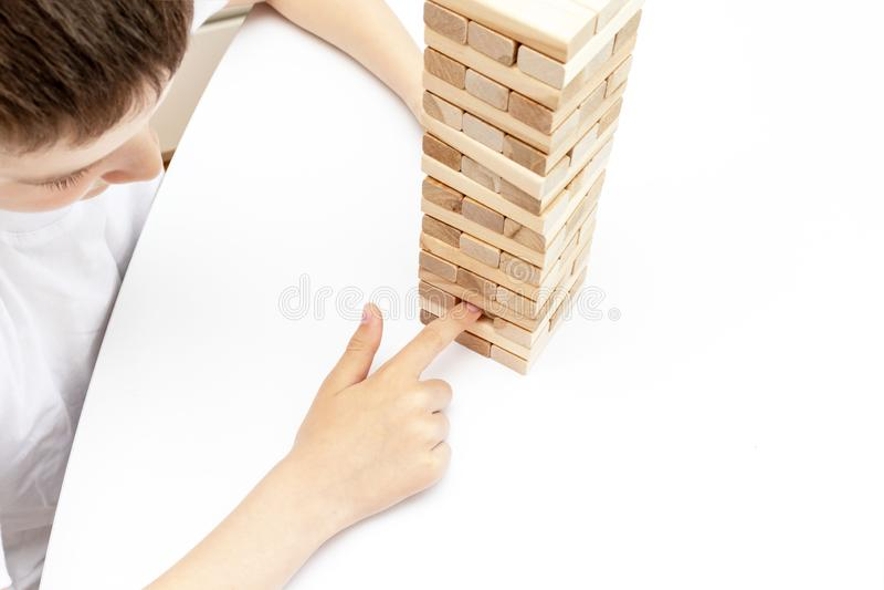 Un ragazzo caucasico preteen che gioca il gioco da tavolo di legno della torre del blocco per la pratica la suoi abilit? e spetta immagine stock