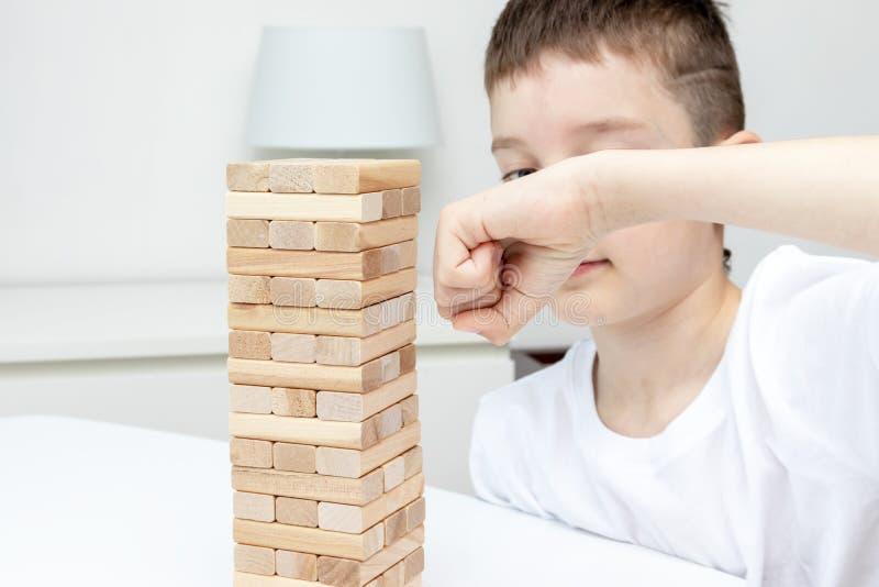 Un ragazzo caucasico preteen che perfora il gioco di legno della torre del blocco con il suo braccio immagine stock
