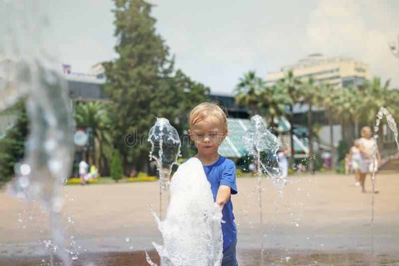 Un ragazzo che gioca con acqua in fontana del parco Estate calda fotografie stock