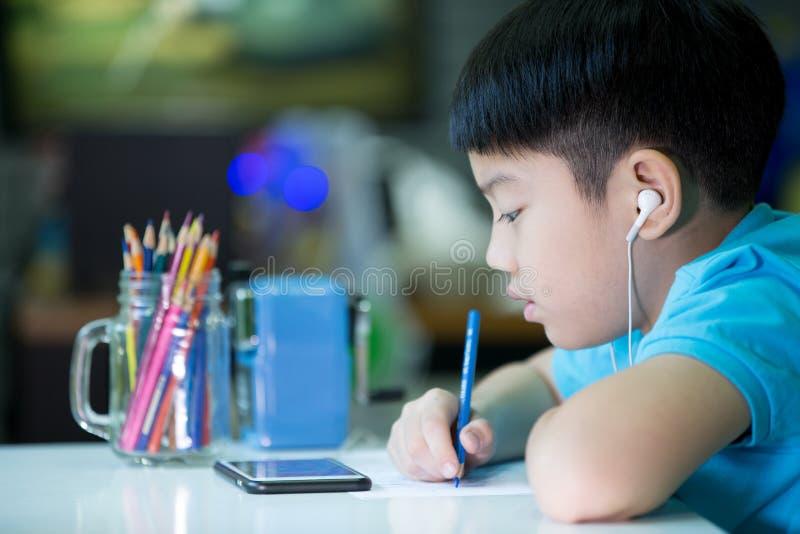 Un ragazzo che per mezzo del cellulare e dipingendo su un Libro Bianco a casa immagine stock libera da diritti
