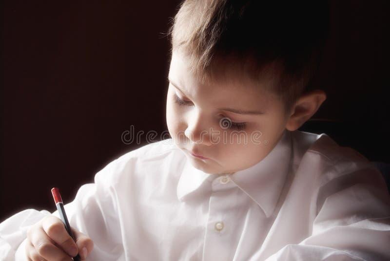 Un ragazzo che scrive una lettera fotografia stock