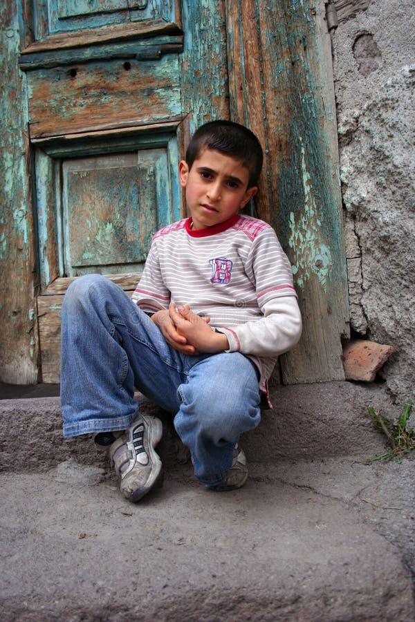 Un ragazzo che si siede al gradino della porta immagine stock