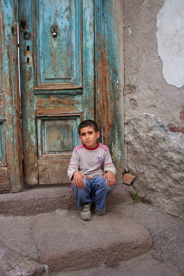 un ragazzo che si siede al gradino della porta fotografie stock