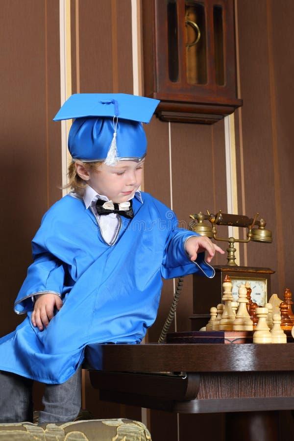 Un ragazzo che si siede su una tavola e che gioca scacchi fotografia stock