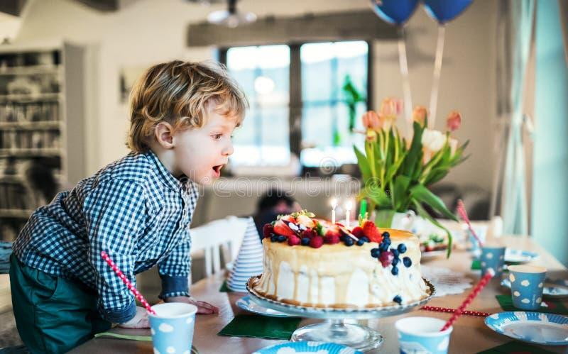 Un ragazzo che sta su una sedia, spegnente le candele su una torta di compleanno fotografia stock libera da diritti