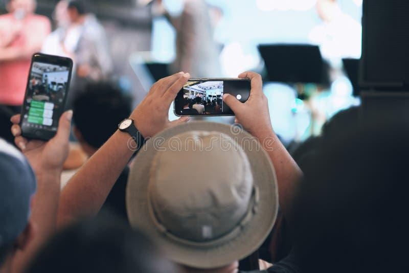 Un ragazzo che utilizza smartphone per la presa un'immagine nel concerto fotografie stock