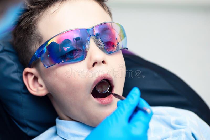 Un ragazzo con gli occhiali di protezione nella sedia dentaria Il medico esamina la cavità orale con uno specchio dentario specia fotografia stock libera da diritti