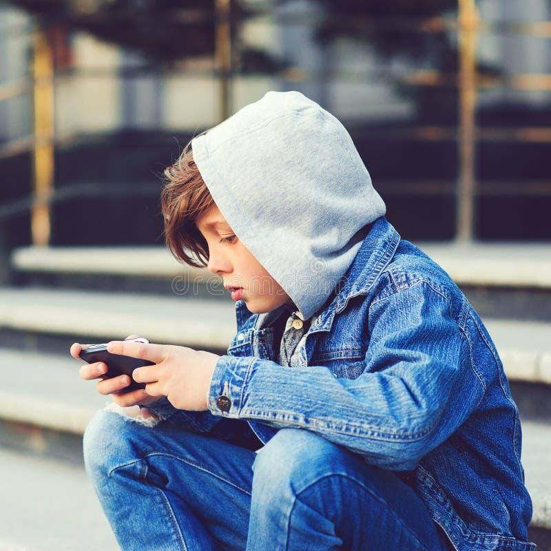 Un ragazzo con uno smartphone seduto sulle scale dopo la scuola Concetto di tecnologia, istruzione e stile di vita Messaggi di te fotografie stock libere da diritti