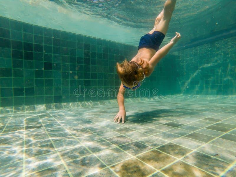 Un ragazzo del bambino sta nuotando underwater in uno stagno, sta sorridendo e trattenendo il respiro, con i vetri di nuoto fotografia stock libera da diritti
