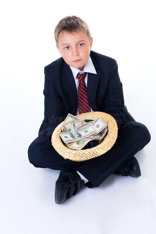 Un ragazzo dell'adolescente in uniforme scolastico che tiene un cappello e che elemosina i soldi fotografie stock libere da diritti