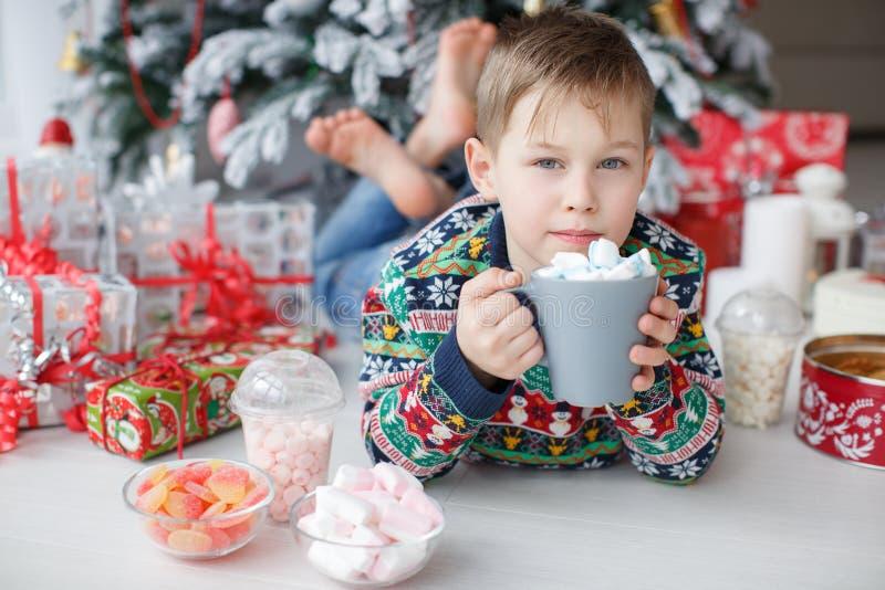 Un ragazzo di 5 anni si trova accanto ad un bello albero di Natale che tiene una grande tazza di caffè con le caramelle gommosa e fotografie stock libere da diritti