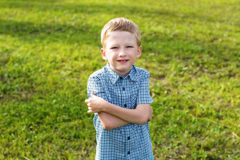 Un ragazzo di sette anni in una camicia di plaid immagine stock