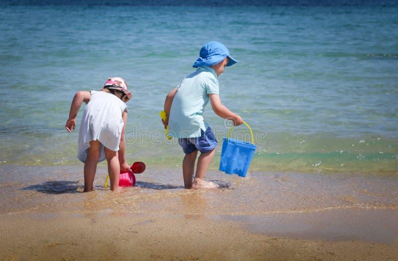 Un ragazzo e una ragazza che giocano con i giocattoli della spiaggia sulla spiaggia fotografia stock