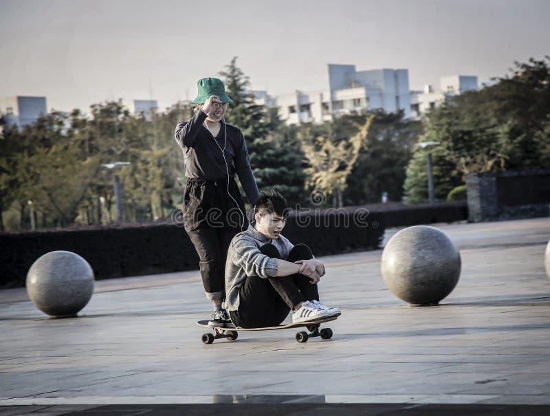 Un ragazzo e una ragazza che pattinano su un singolo pattino fotografia stock libera da diritti