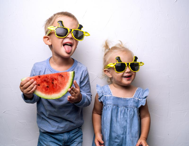 Un ragazzo e una ragazza felici in occhiali da sole gialli mangiano un'anguria rossa matura su un ventilatore a muro bianco Ritra fotografia stock