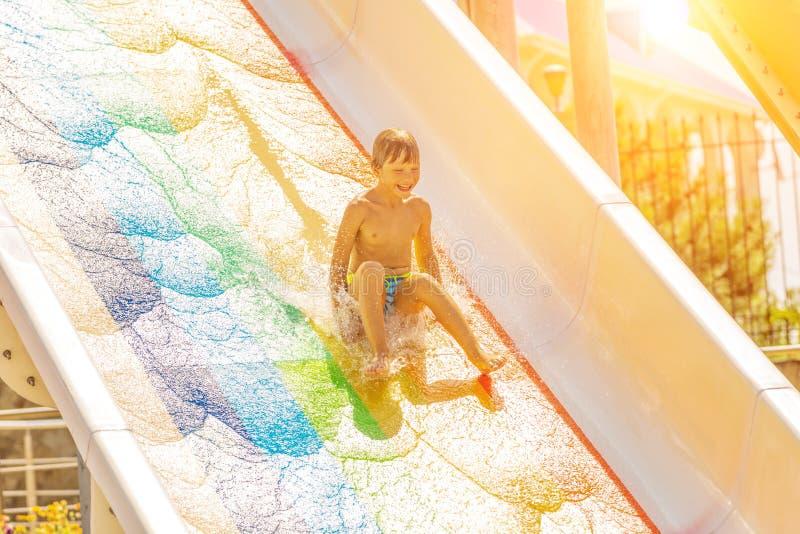 Un ragazzo felice sull'acquascivolo in una piscina che si diverte durante le vacanze estive in bella acqua parcheggia un ragazzo fotografie stock