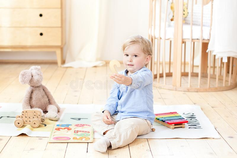 Un ragazzo gioca con i giocattoli di legno e mostra il numero 2 Giocattoli di legno educativi per un bambino Ritratto di un ragaz fotografie stock