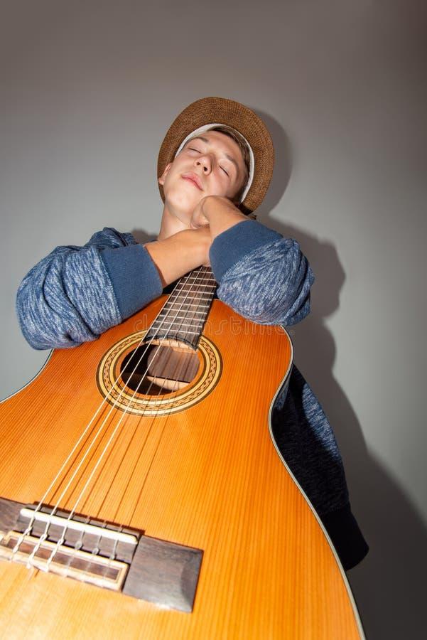 Un ragazzo gioca la chitarra su un fondo grigio nello studio, foto grandangolare del primo piano immagini stock libere da diritti