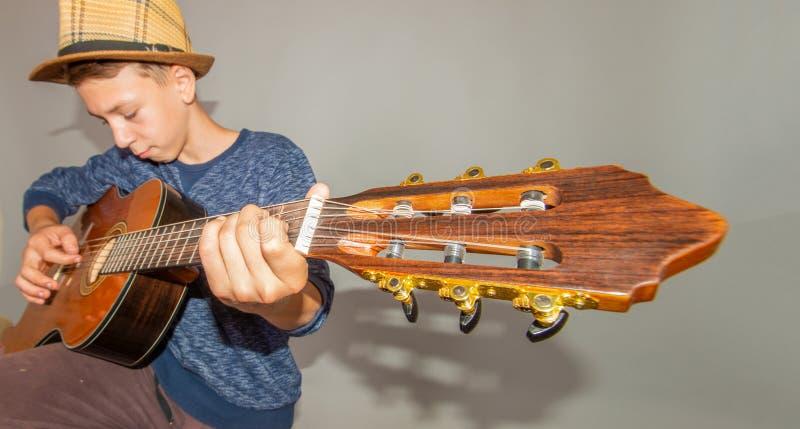 Un ragazzo gioca la chitarra su un fondo grigio nello studio, foto grandangolare del primo piano immagine stock libera da diritti