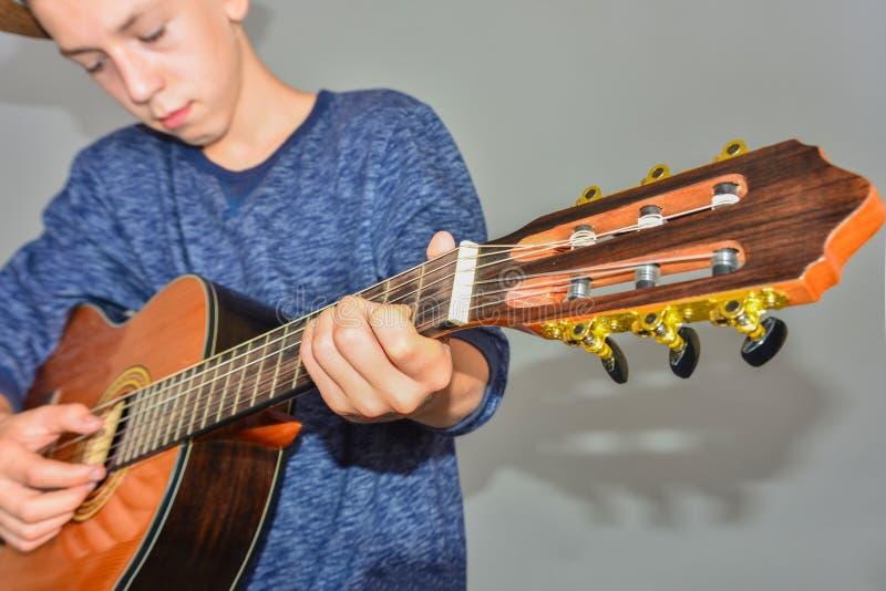 Un ragazzo gioca la chitarra su un fondo grigio nello studio, foto grandangolare del primo piano fotografia stock libera da diritti
