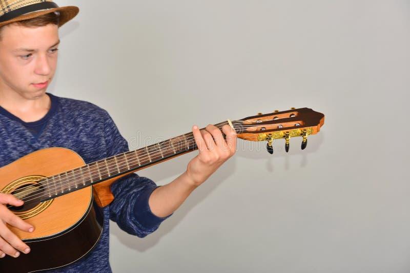Un ragazzo gioca la chitarra su un fondo grigio nello studio, foto grandangolare del primo piano fotografia stock