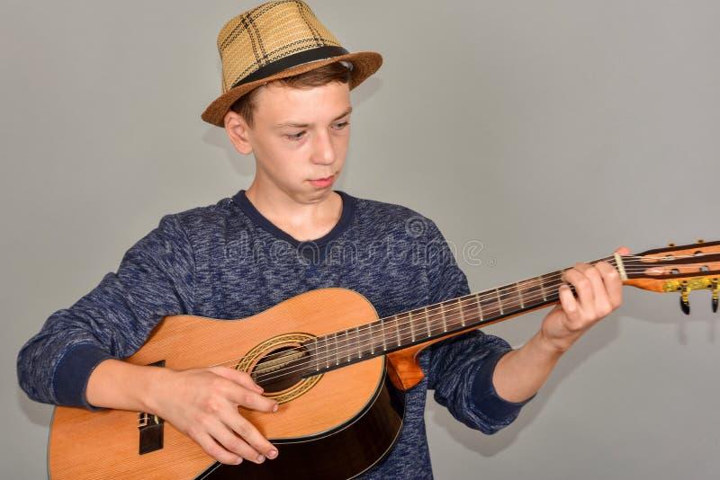 Un ragazzo gioca la chitarra su un fondo grigio nello studio, foto grandangolare del primo piano immagini stock