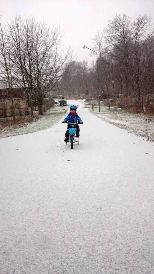 Un ragazzo gode di di ciclare nell'inverno immagine stock