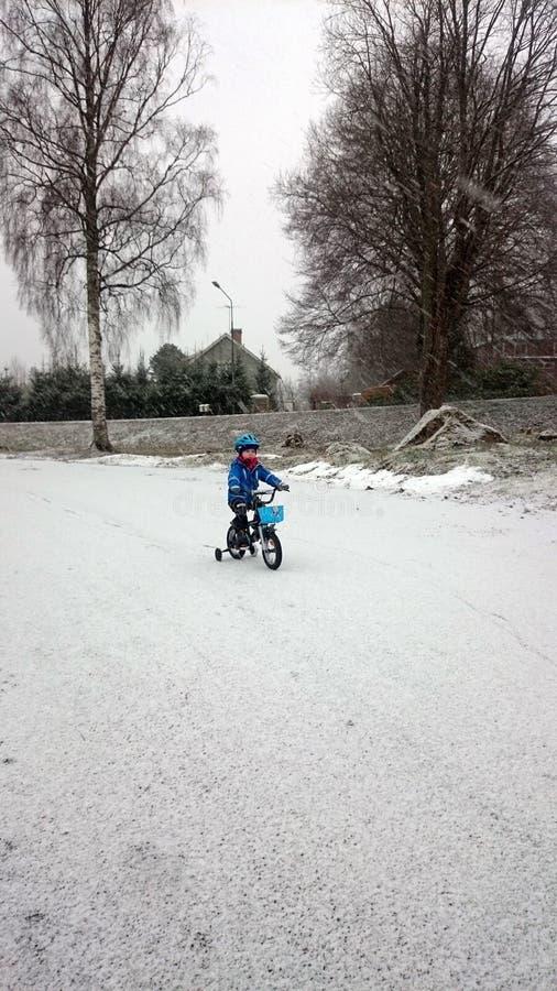 Un ragazzo gode di di ciclare nell'inverno immagine stock libera da diritti