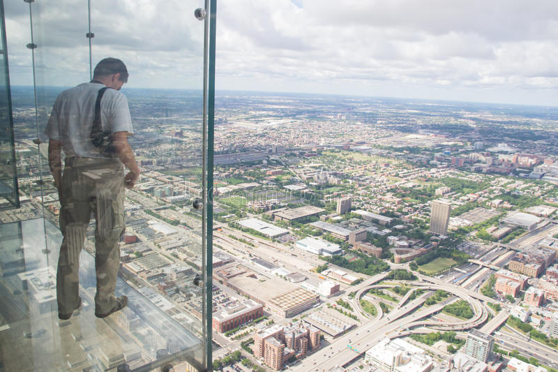 Un ragazzo guarda fuori dal balcone trasparente della torre di willis del Th fotografie stock