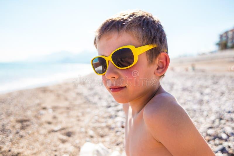 Un ragazzo nei giochi degli occhiali da sole sulla spiaggia fotografie stock