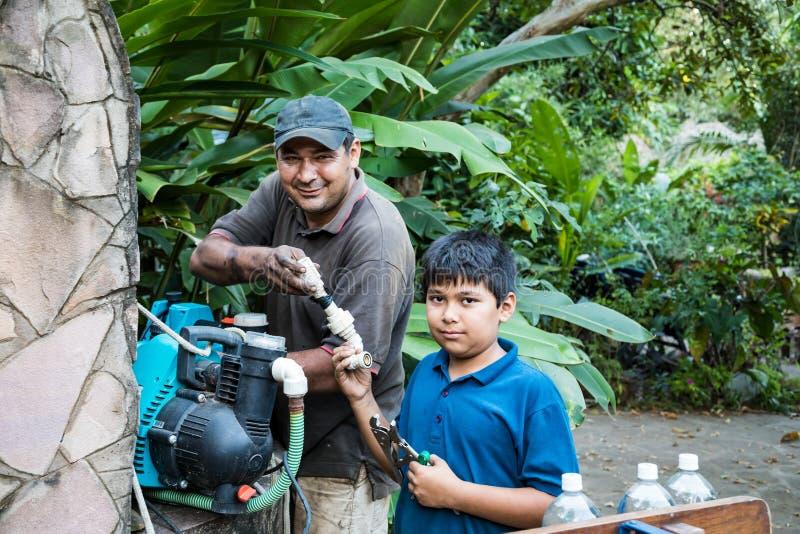 Un ragazzo paraguaiano aiuta suo padre a riparare una pompa fotografie stock