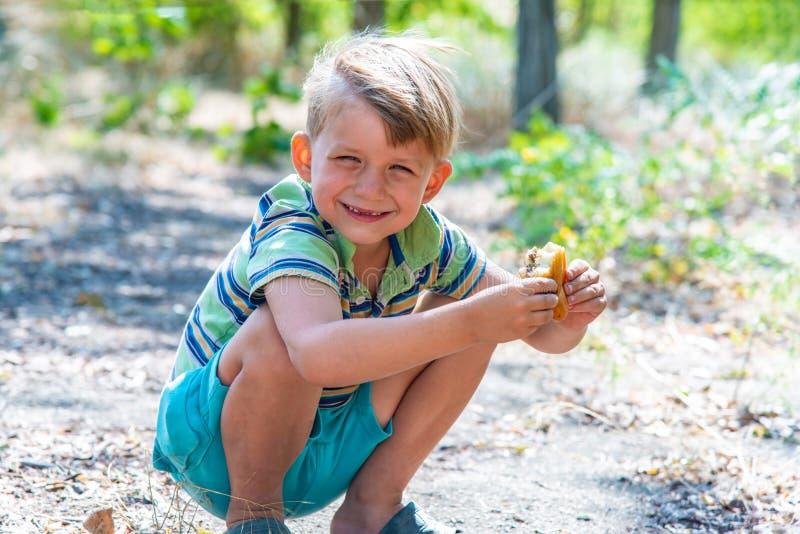 Un ragazzo sta mangiando un panino nel legno, occupante immagine stock libera da diritti