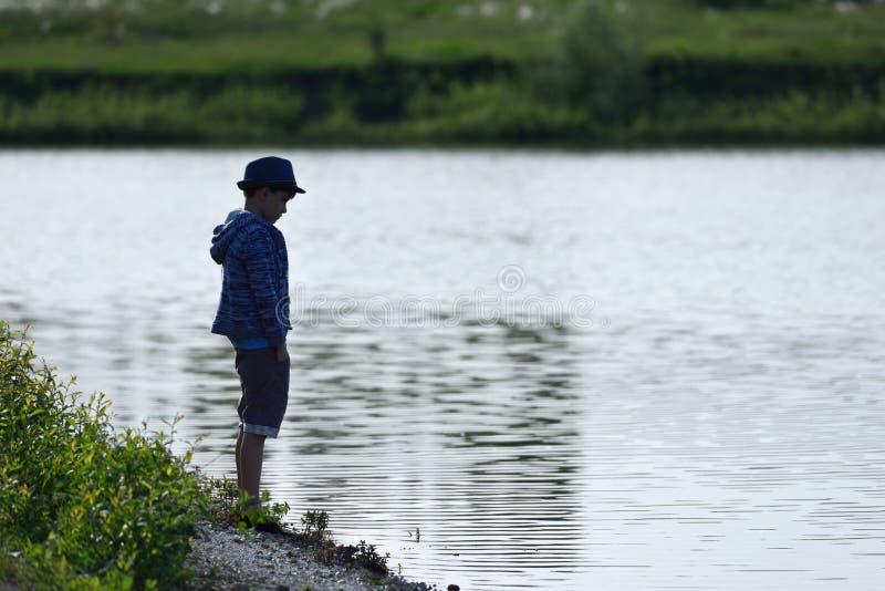 Un ragazzo sta vicino ad un fiume e guarda tristemente nell'acqua immagine stock libera da diritti