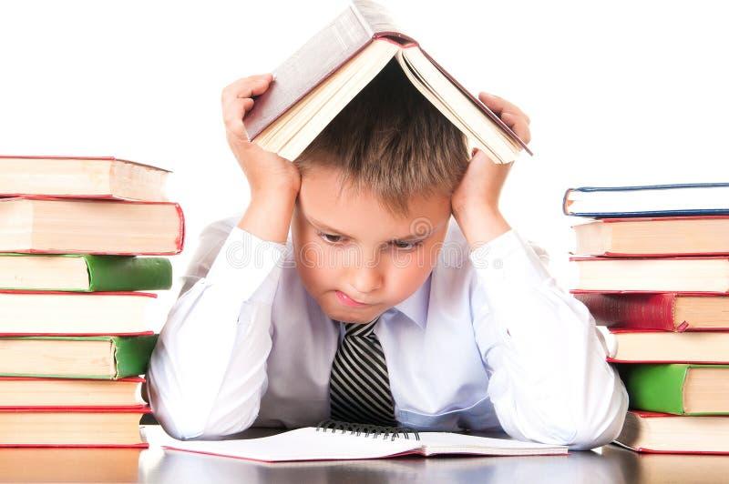 Un ragazzo stanco e ritardante dello scolaro si siede in una biblioteca con i libri ed impara le lezioni Riluttanza imparare fotografia stock libera da diritti