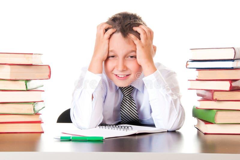 Un ragazzo stanco e ritardante dello scolaro si siede in una biblioteca con i libri ed impara le lezioni Riluttanza imparare fotografia stock