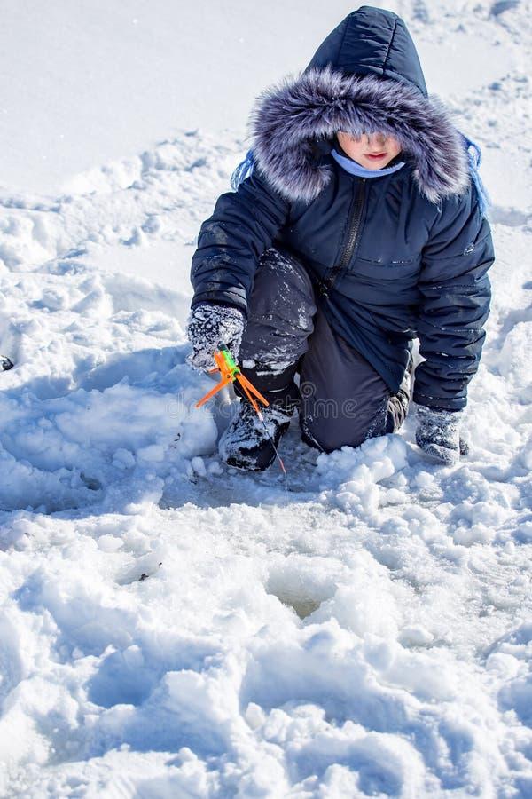 Un ragazzo su ghiaccio sta pescando nell'inverno immagini stock