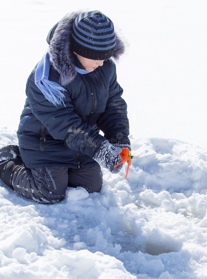 Un ragazzo su ghiaccio sta pescando nell'inverno fotografia stock