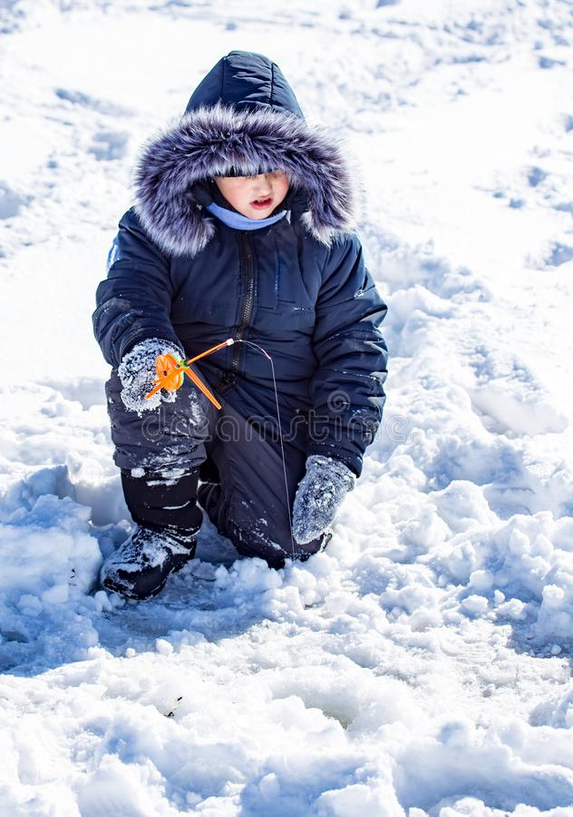 Un ragazzo su ghiaccio sta pescando nell'inverno immagine stock